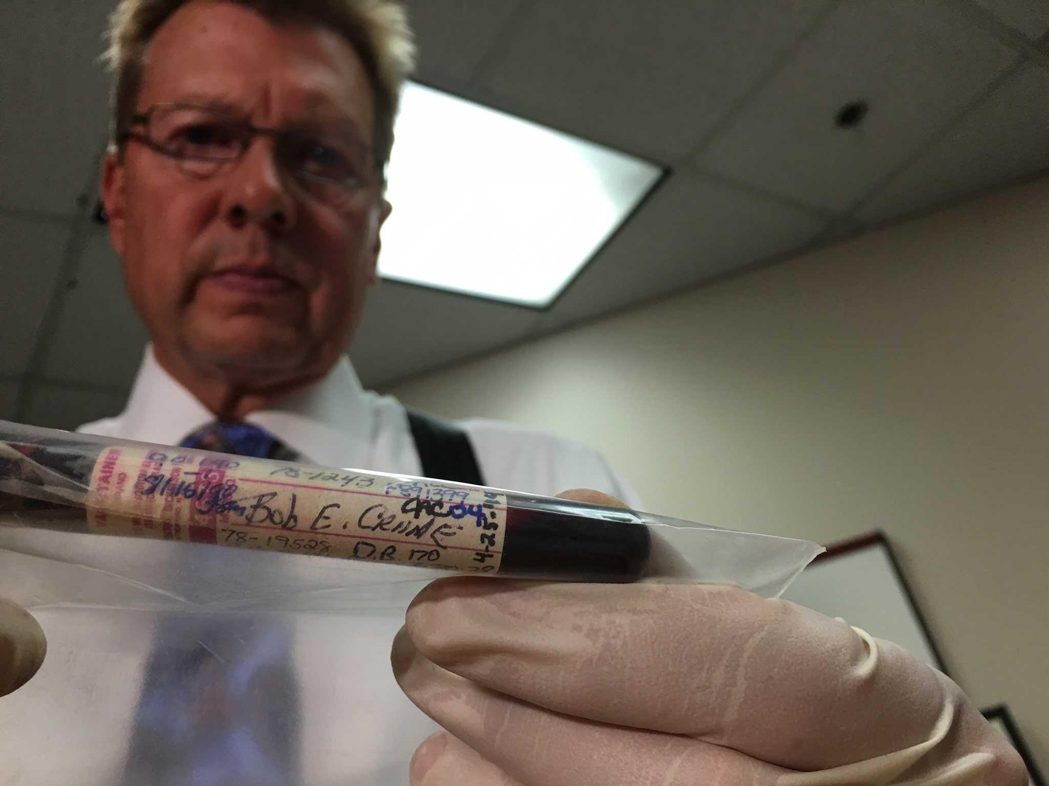 "John Hook, author of ""Who Killed Bob Crane?"" holding a vial of Bob Crane's blood."